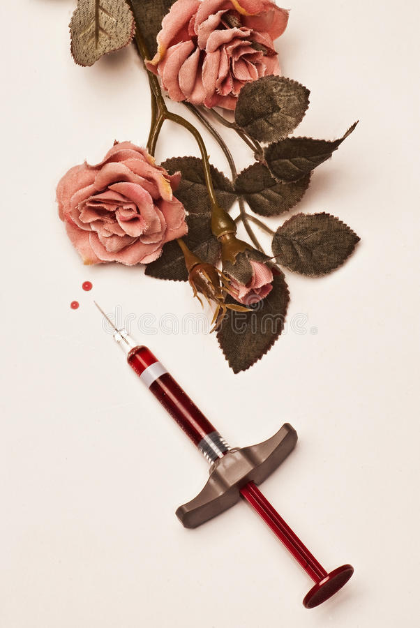 The seringe and the roses. A seringe filled with a red fluid, some roses and two drop of red fluid on a white background royalty free stock images