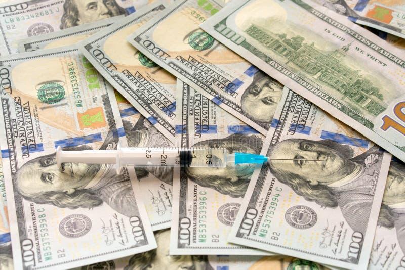 Seringue et argent - coûts de concept de traitement photographie stock libre de droits