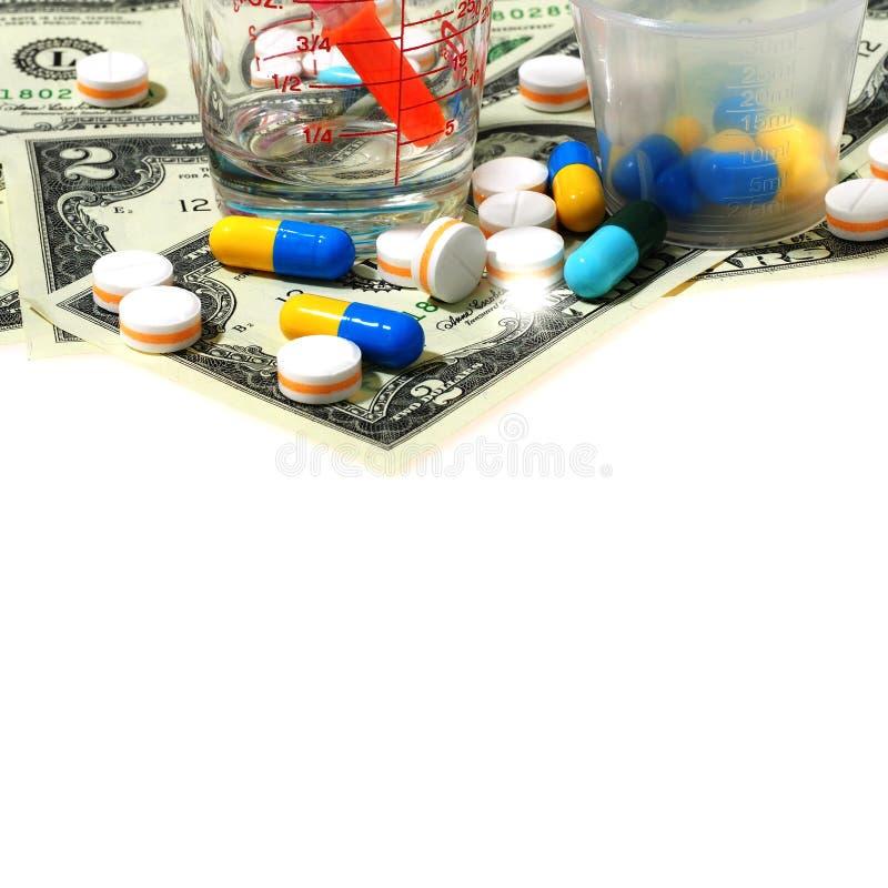 Seringue et beaucoup de pilules sur le billet d'un dollar d'isolement sur le backgrou blanc photographie stock