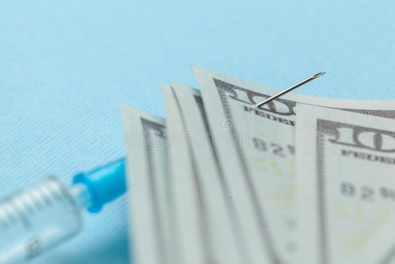 Seringue et dollars de papier goupill?s ? l'aiguille sur le fond bleu Assurance-maladie ch?re photographie stock