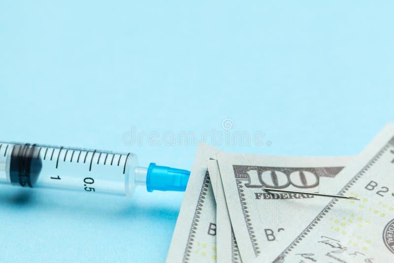 Seringue et dollars de papier goupill?s ? l'aiguille sur le fond bleu Assurance-maladie ch?re Copiez l'espace pour le texte images stock