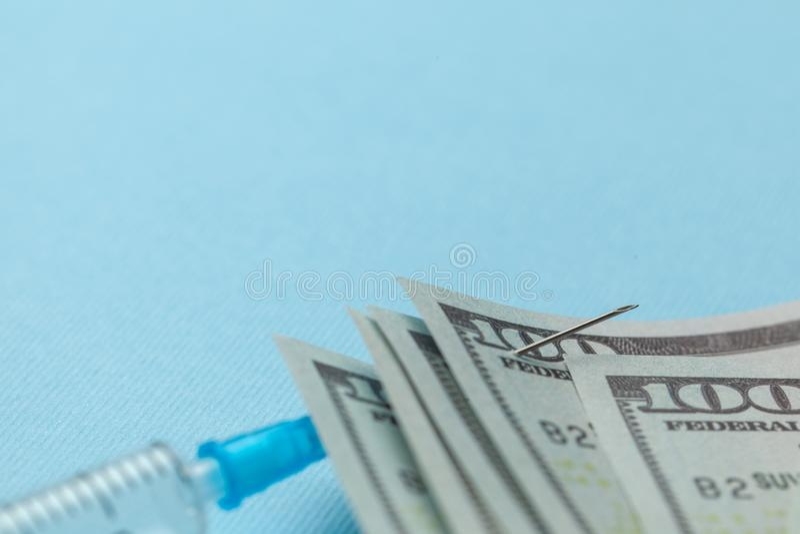 Seringue et dollars de papier goupill?s ? l'aiguille sur le fond bleu Assurance-maladie ch?re Copiez l'espace pour le texte photographie stock libre de droits