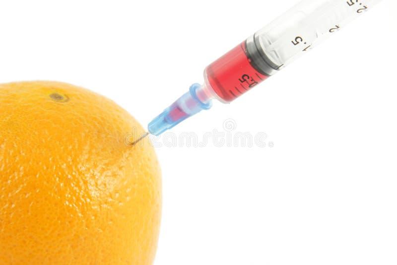 Seringue injectant dans l'orange photos stock