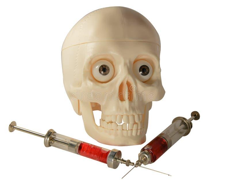 Seringue squelettique de crâne avec la médecine photographie stock