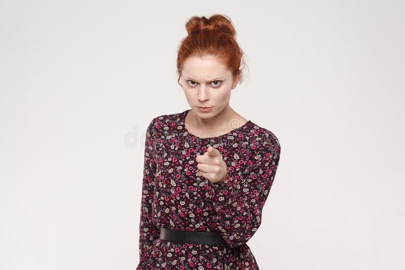 The seriosly redhead woman wearing flowers dress, pointing finger at camera. royalty free stock photos