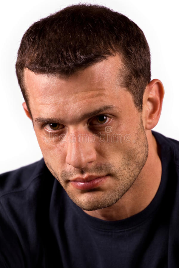 So serious. A serious young man looks directly at the camera stock photo