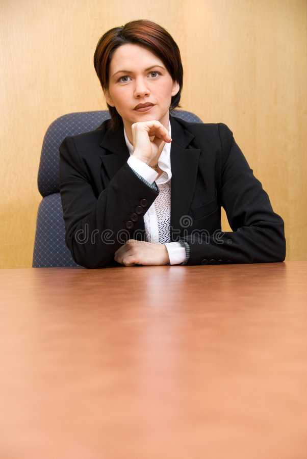 Serious. Business woman in a boardroom table royalty free stock image
