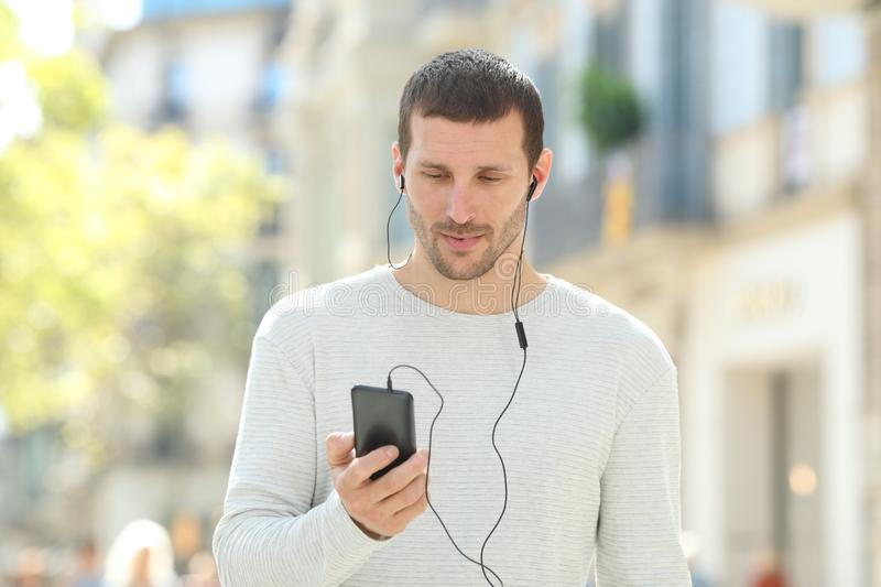 Serious adult man listening to music on phone in the street. Front view portrait of a serious adult man listening to music on phone wearing earbuds in the street stock photo