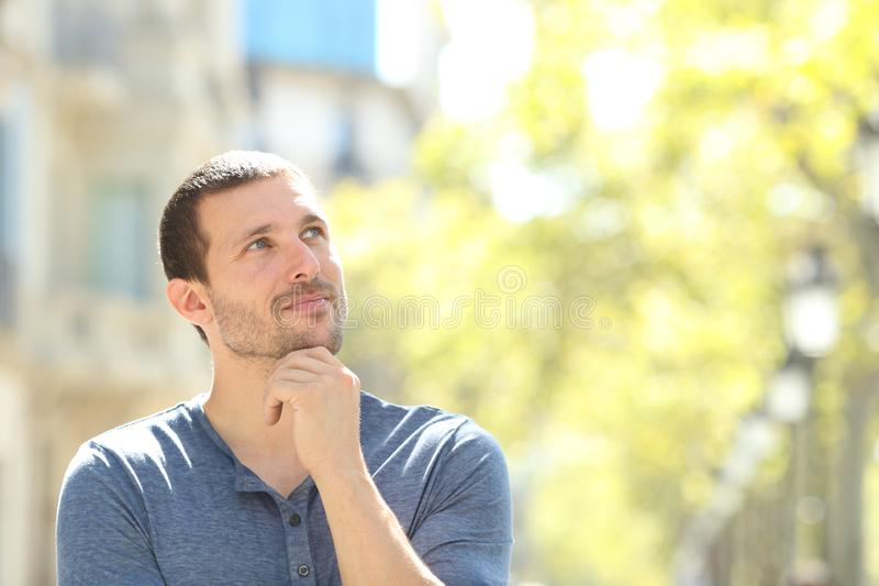 Serious adult man thinking looking at side in the street royalty free stock image