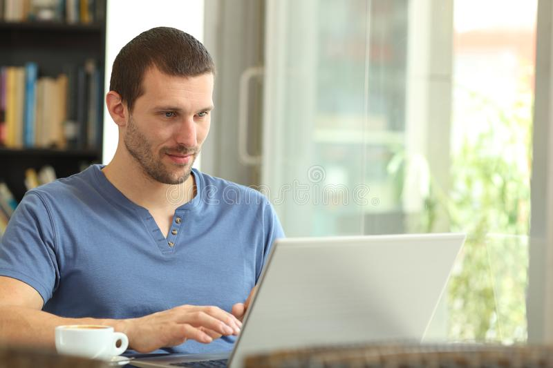 Serious adult man using a laptop browsing web. Sitting in a coffee shop or home stock photo