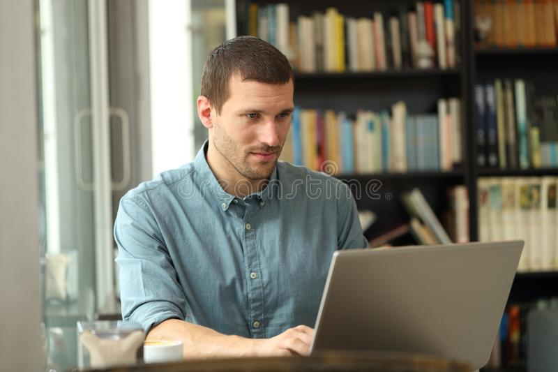 Serious adult man writing on laptop in a coffee shop royalty free stock images