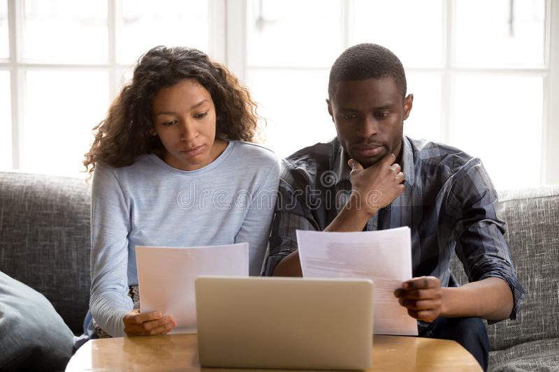 Serious African American couple reading paper documents royalty free stock image