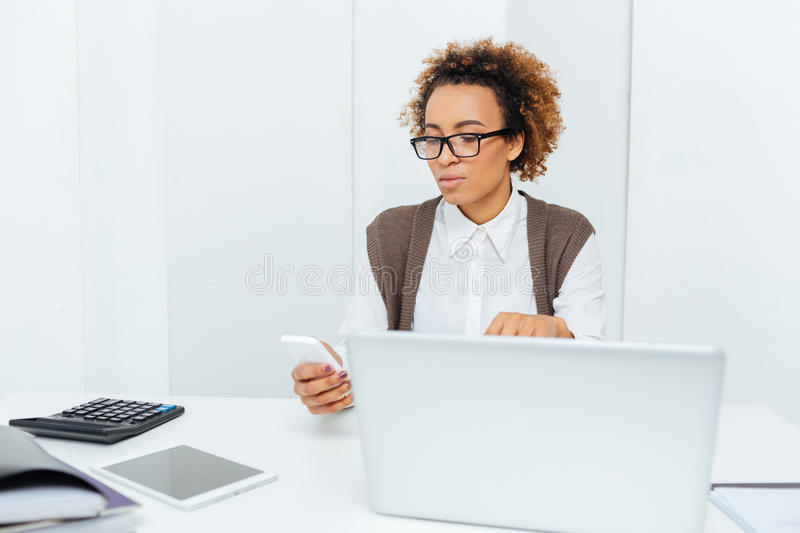 Serious african american woman accountant using laptop and smartphone stock images