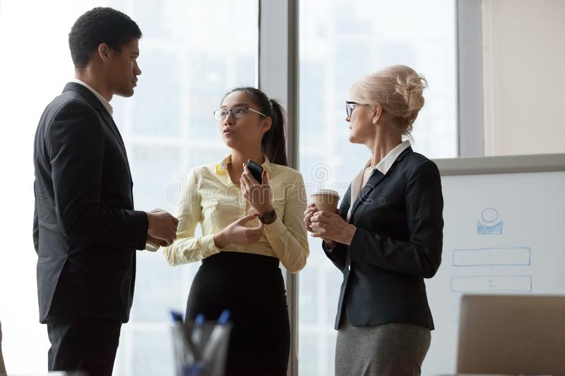 Serious african asian and caucasian colleagues talking at work break stock image