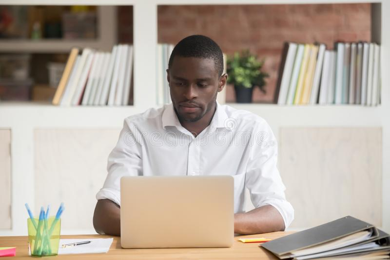 Serious african businessman sitting at desk typing on computer stock images