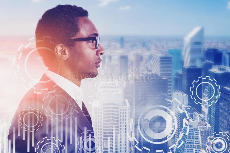 Serious African man in city, gears. Serious young African American businessman in glasses standing in city with double exposure of gears and graphs. Toned image royalty free stock images