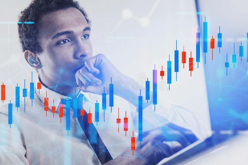 Serious African man with laptop, graph. Serious young African American businessman working with laptop in office with double exposure of graphs. Concept of stock image