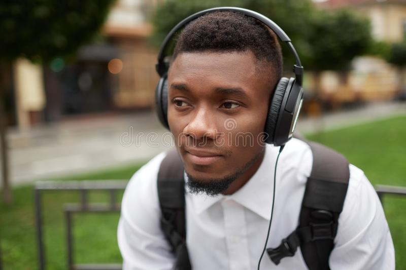 Serious african man listening music in big headphones. royalty free stock photo