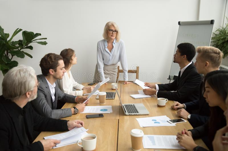 Serious aged businesswoman leading corporate team meeting talkin stock photo