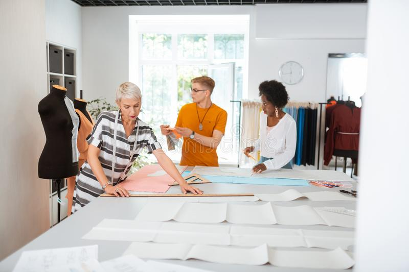 Serious aged female designer making a paper pattern royalty free stock photo