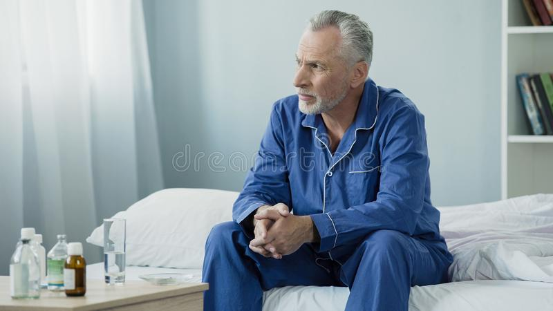 Serious aged man sitting upset and pensive on bed at home, lonely sick person stock photos