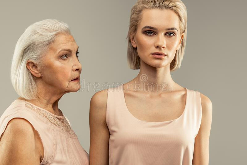 Serious aged woman looking at her daughter stock images
