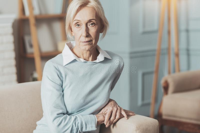 Serious aged woman looking at you royalty free stock photo