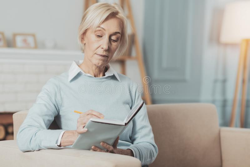 Serious aged woman planning her time stock photography