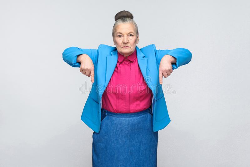 Serious aged woman pointing fingers at copy space royalty free stock image