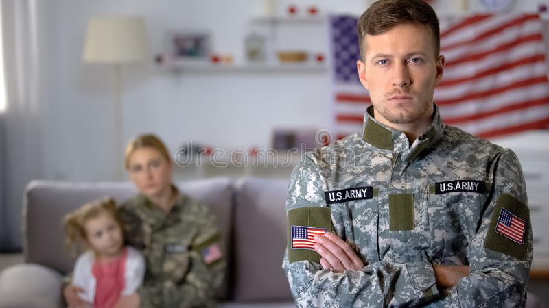 Serious american soldier looking at camera daughter and military wife background. Stock photo royalty free stock image