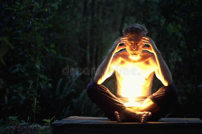 A serious, angry man sits in the dark outside with a bright light lamp on his lap. Pain, depression, stress or hatred concept stock images