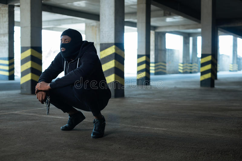 Serious armed man holding waiting for somebody. Crime in the city. Nice serious armed man holding a gun and waiting for somebody while squatting stock image