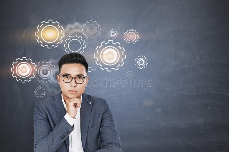 Serious Asian businessman, gears and cogs. Serious Asian businessman in glasses sitting near blackboard with gears drawn on it. Concept of brainstorming. Mock up stock image