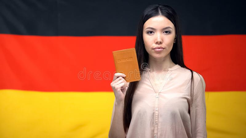Serious Asian female showing passport against German flag background, close-up stock images