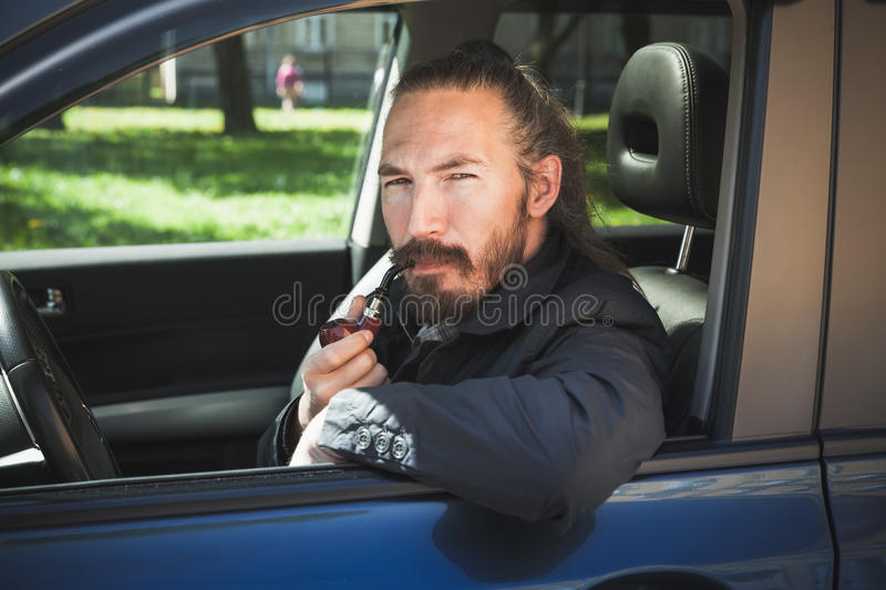 Serious Asian man smoking pipe. Driver. Of modern Japanese crossover suv car, portrait in open car window stock photography