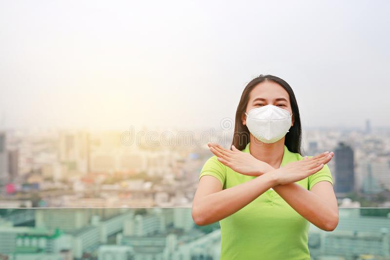 Serious Asian woman wearing a protection mask with making X sign with her arms to stop PM 2.5 air pollution in Bangkok city. royalty free stock image