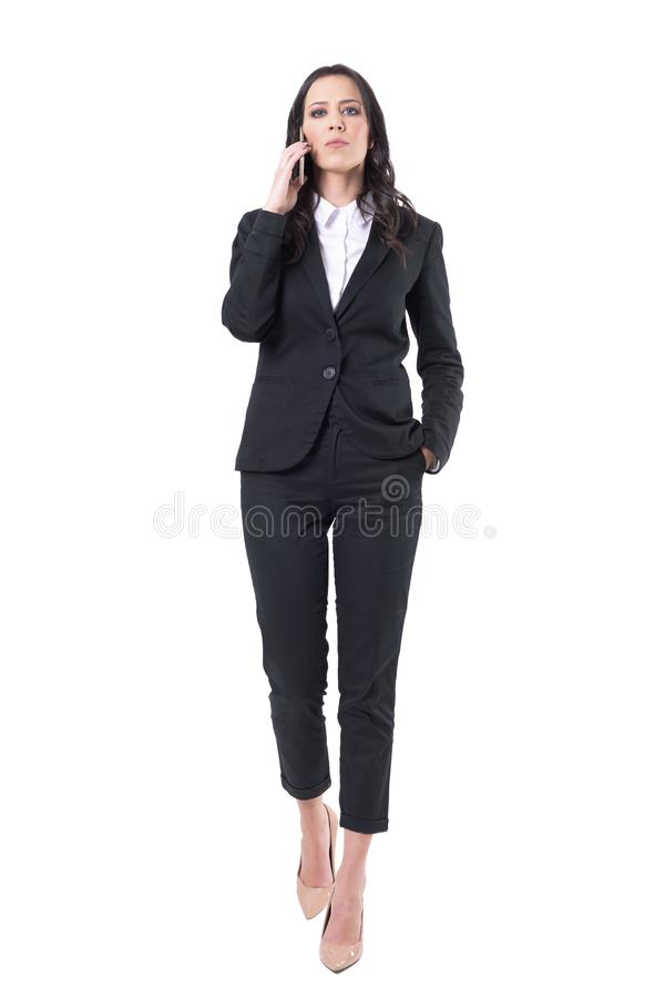 Serious attitude bossy business woman talking on the mobile phone walking towards camera. stock image