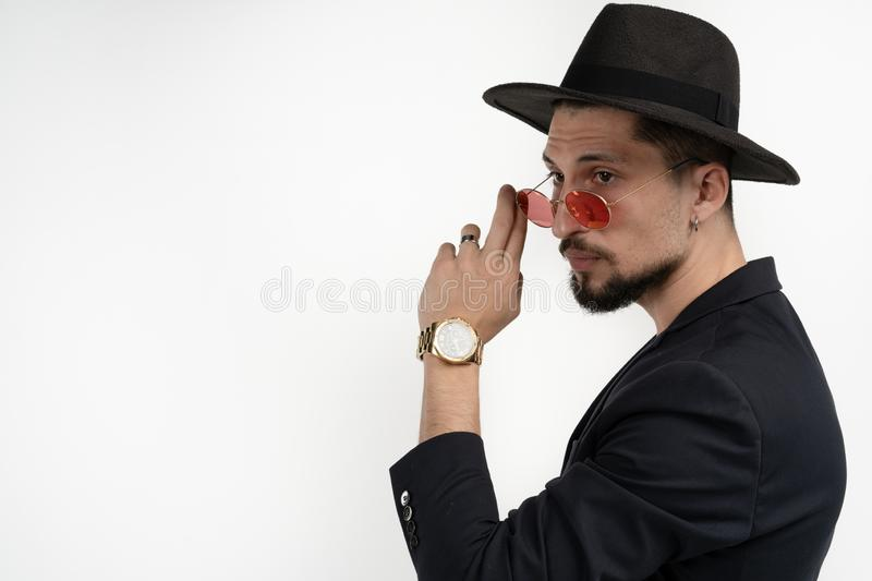 Serious attractive bearded man in black suit and hat, touching red sunglasses, posing isolated over white background royalty free stock photo