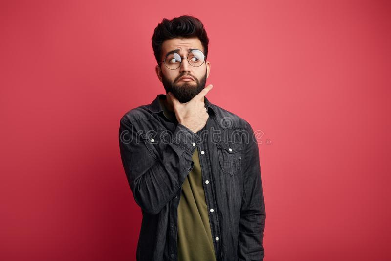 Serious attractive bearded stylish man touching chin and looking aside at camera stock photography