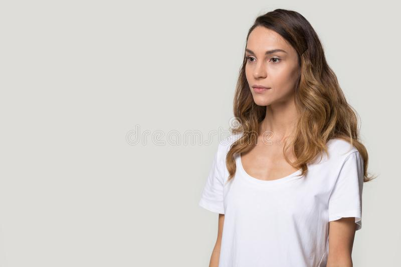 Serious attractive woman posing in studio aside over gray background. Thoughtful woman with curly hairs in white t-shirt posing in studio standing aside of blank stock photography