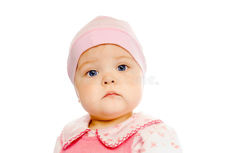 Serious baby in a pink hat on a white background. Portrait of a serious baby in a pink hat on a white background royalty free stock photo