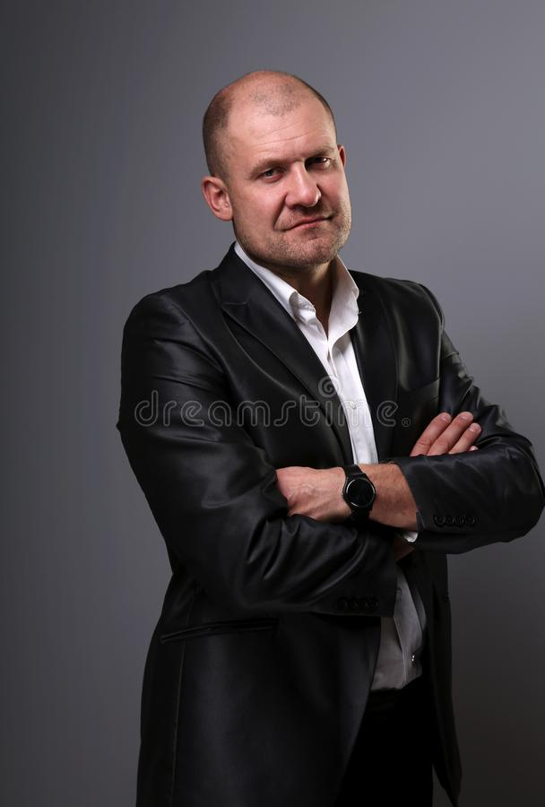Serious bald thinking business man with folded arms in suit on grey background. Closeup royalty free stock photography