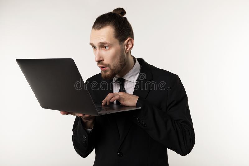 Serious bearded businessman or teacher in black suit reading post at notebook royalty free stock photos