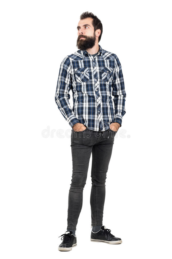Serious bearded hipster in checked plaid shirt with hands in pockets looking away stock photo