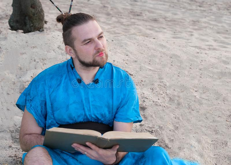 serious bearded man with bun on head in blue kimono sitting, holding large book royalty free stock photography