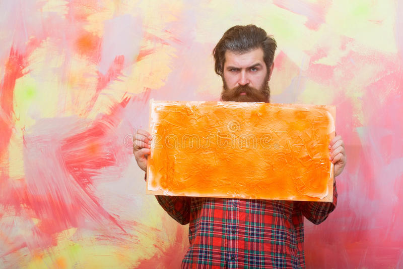 Serious bearded man holding orange oil paint texture on canvas royalty free stock image
