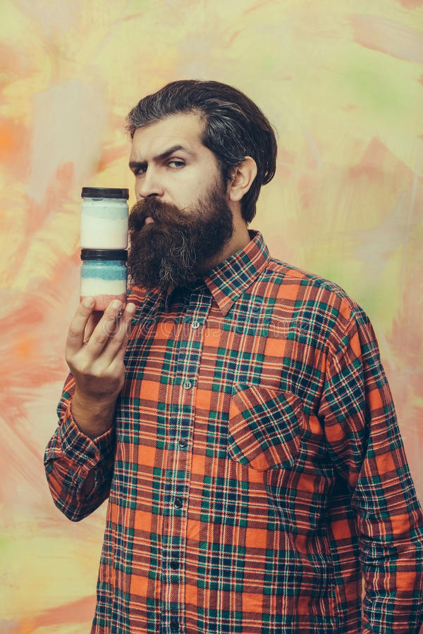 Serious bearded man holding two cosmetic jars royalty free stock image