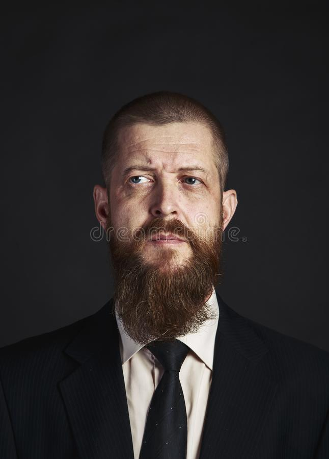 Serious , bearded man in white shirt and classic, elegant jacket on dark background stock photography