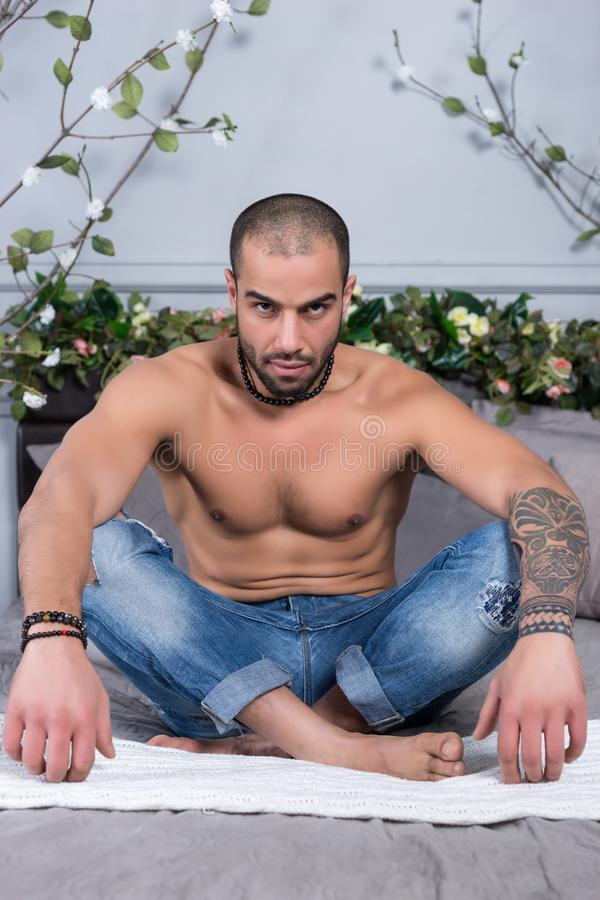 Serious bearded muslim man with bare chest and with tattooed han stock photo