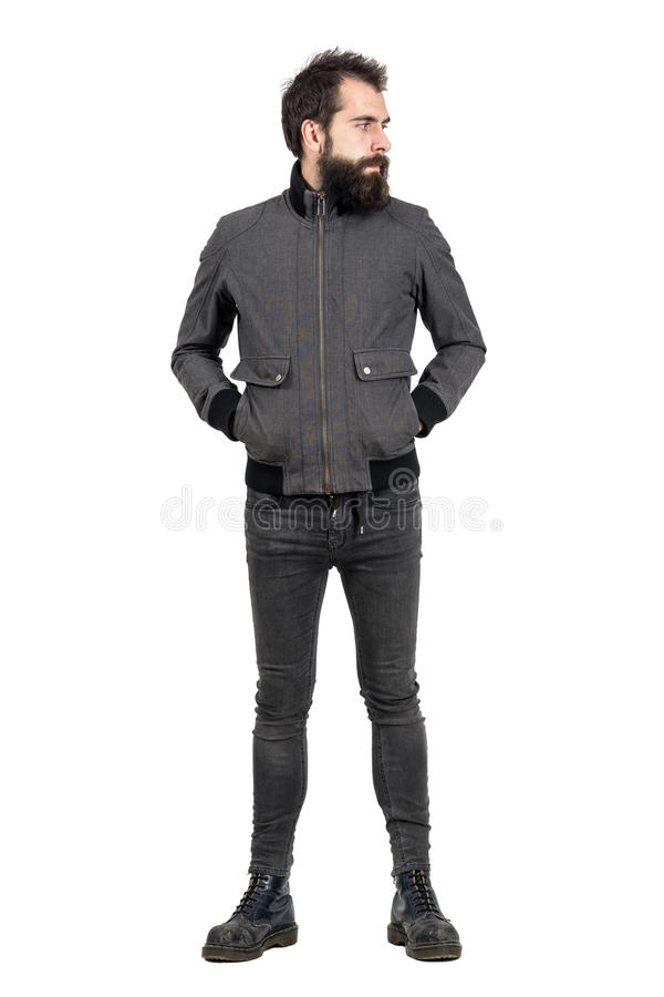 Serious bearded punker in gray jacket, tight jeans and old army boots looking away. Full body length portrait isolated over white studio background stock image